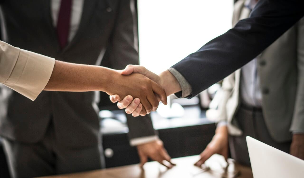 Businesspeople shaking hands | PCI compliance