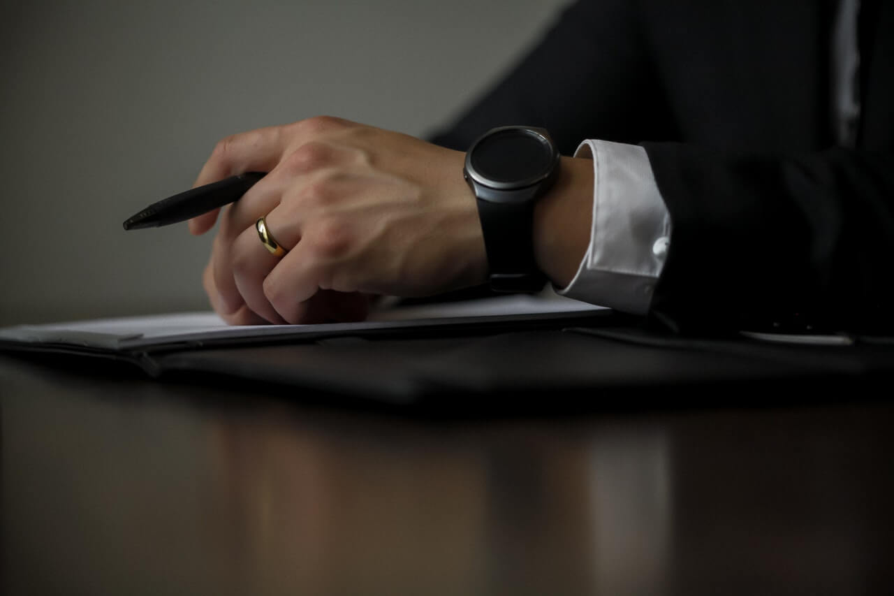 Businessperson writing with a pen in hand